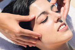 Facial massage. Delicate and relaxing facial massage in spa club Stock Image