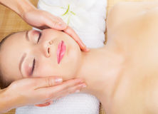 Facial massage. Beautiful young woman receiving facial massage with closed eyes in a spa salon Stock Images