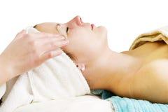 Facial Massage. A woman receiving a facial massage at a beauty spa Stock Photography