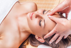 Facial massage. Beautiful young woman receiving facial massage with closed eyes in a spa salon royalty free stock photo