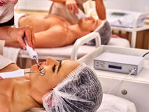Facial massage at beauty salon. Electric stimulation couple skin care. Royalty Free Stock Images