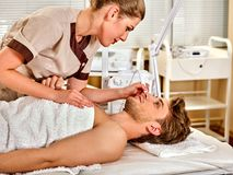 Facial massage at beauty salon. Electric stimulation man skin care. Stock Image