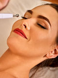 Facial massage at beauty salon. Electric stimulation woman skin care. Electronic facial lift massage at beauty salon. Electric stimulation skin care of woman Royalty Free Stock Image