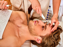 Facial massage at beauty salon. Electric stimulation woman skin care. Royalty Free Stock Image