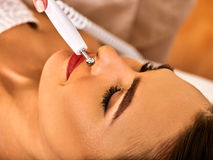 Facial massage at beauty salon. Electric stimulation woman skin care. Stock Image
