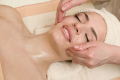 Facial massage with massagin oil. Young beautiful woman having facial massage with massagin oil Royalty Free Stock Photo