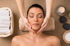 Facial Massage At Spa. Beautiful Latin Woman Getting Facial Massage At Spa royalty free stock photography