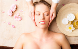 Facial massage at spa studio. On massage table Stock Photography