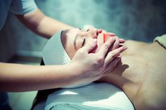 Facial massage treatment by professional at cosmetics saloon Stock Images