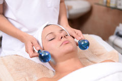 Facial massage. Young woman getting facial massage in the spa Stock Image