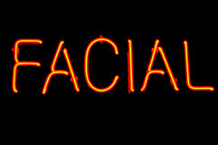 Facial Neon Sign. Red neon sign advertising facials Royalty Free Stock Images