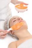 Facial orange alginate mask applying Royalty Free Stock Photo