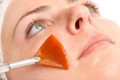Facial peeling mask applying. Beauty salon, facial peeling mask with retinol and fruit acids Stock Photos