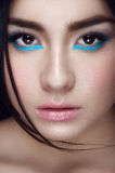 Facial portrait of asian young girl. With blue wings under hazel eyes and open lips looking at you on black background Royalty Free Stock Photography
