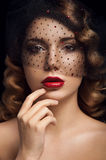Facial portrait of lady with brown eyes. Deep red lipstick, two nevus on her left cheek, curly hair and veil with black dots and rubies. Touching her lips Stock Photo