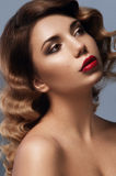 Facial portrait of young beauty girl with brown eyes. Dark brown eye-shadows and deep red lipstick, two nevus on her right cheek. Ambre effect on her hair and Royalty Free Stock Image