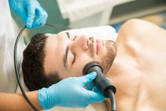 Facial rejuvenation therapy in a spa. Closeup of a handsome young men getting facial rejuvenation therapy in a health spa Royalty Free Stock Photos