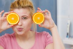 Woman having gel mask on face holding orange. Facial skin and body care, vitamins good complexion treatment at home concept. Young woman having gel mask on her Stock Photography
