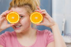 Woman having gel mask on face holding orange. Facial skin and body care, vitamins good complexion treatment at home concept. Young woman having gel mask on her Stock Photos