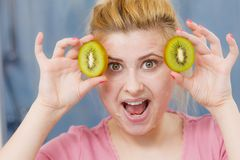 Woman having gel mask on face holding kiwi. Facial skin and body care, vitamins good complexion treatment at home concept. Young woman having gel peel off mask Stock Images