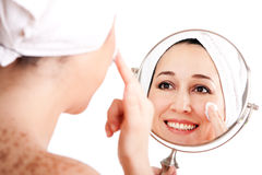 Facial skincare anti-ageing exfoliation. Beautiful happy smiling woman face applying exfoliating cream as anti-aging skincare treatment while looking at mirror Stock Photography