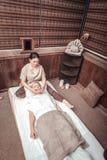 Top view of an Asian woman doing facial massage. Facial therapy. Top view of a skilled Asian women doing facial massage for her client stock image