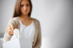 Facial tissue. Young woman taking facial tissue from a box Royalty Free Stock Photography