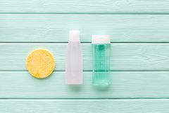 Facial tonic, lotion and sponge for face care on mint green wooden background top view mock up stock photos