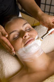 Facial treatment. A beautician applying a facial treatment mask and the young woman is relaxing Stock Photo