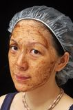 Facial Treatment. Mud facial treatment on Chinese young lady Stock Photo