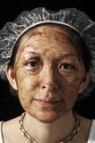 Facial Treatment. Mud facial treatment on Chinese young lady Stock Image