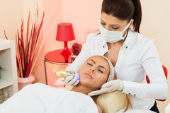 Facial treatment. A beautiful women receiving a facial treatment Royalty Free Stock Image