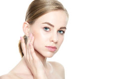 Facial treatment. Cosmetology, beauty and spa concept. Isolated on white background. Beautiful Young Blond Woman with Perfect Skin touching her face. Facial Royalty Free Stock Photography