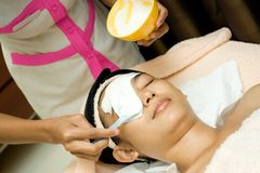 Facial treatment with mask cream royalty free stock images