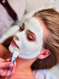 Facial treatment of woman. Clay face mask and beautician hands. Royalty Free Stock Photos