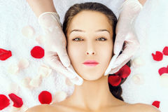 Facial treatment. Young woman receiving spa facial treatment Royalty Free Stock Photography