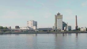 Facilidades de planta concretas perto da entrada no rio no tempo ensolarado video estoque