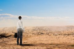 Facing bad times. Mixed media. Businessman with suitcase in dry cracked desert. Mixed media Royalty Free Stock Images