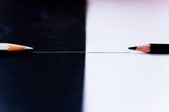 Facing black white pencils, competition metaphor. Conceptual shot depicting contrast through black and white pencils facing each other Royalty Free Stock Image