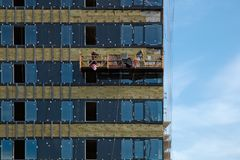 Facing the building with a ventilated facade and hoist with workers. Modern facades of high-rise buildings. Construction of a large residential complex royalty free stock image