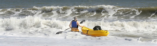 Facing a Challange. Middle aged man with a canoe facing the challange of crossing the rough surf Stock Photo