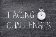Facing challenges watch. Facing challenges phrase written on chalkboard with vintage precise stopwatch royalty free stock photos