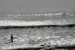 Facing Daunting Challenges. A surfer gets ready to hit the heavy surf in California royalty free stock photography