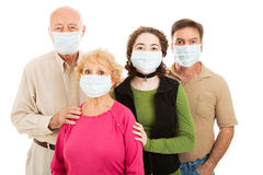 Facing an Epidemic. Family - elderly parents, their adult son, and teen granddaughter - wearing surgical masks to protect from an epidemic Stock Photos