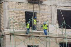 Facing of facade of the building, workers-builders Stock Photo