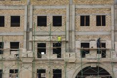 Facing of facade of the building, workers-builders Royalty Free Stock Photo