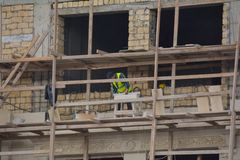 Facing of facade of the building, workers-builders Stock Photography