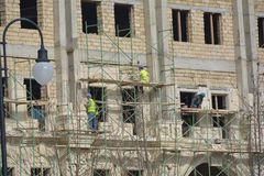 Facing of facade of the building, workers-builders Stock Photos