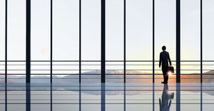 Facing next successful day. Back view of businessman looking on sunrise in office window Royalty Free Stock Photo