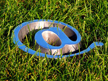 Facing the sky. An at symbol laying down on the grass facing the blue sky Stock Photos